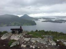 Muchacho que se sienta en la montaña que toma una rotura y que disfruta de la visión Imagen de archivo libre de regalías