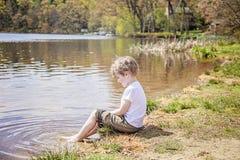 Muchacho que se sienta en la orilla del lago imagenes de archivo