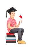 Muchacho que se sienta en la pila de libros y que sostiene el diploma Imagen de archivo libre de regalías