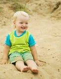 Muchacho que se sienta en la playa de la arena Imagenes de archivo