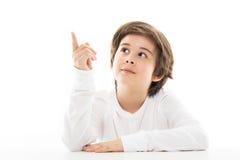 Muchacho que se sienta en la tabla que mira para arriba Fotografía de archivo libre de regalías