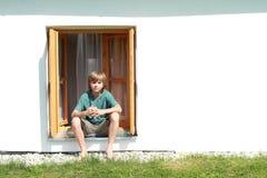 Muchacho que se sienta en la ventana Fotografía de archivo libre de regalías