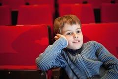 Muchacho que se sienta en las butacas en el cine Imágenes de archivo libres de regalías