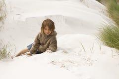 Muchacho que se sienta en las dunas Imagenes de archivo
