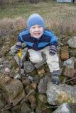 Muchacho que se sienta en las rocas Fotografía de archivo