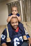 Muchacho que se sienta en los hombros del papá. imagen de archivo libre de regalías