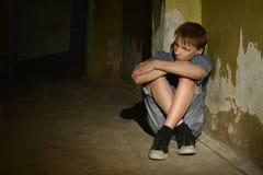Muchacho que se sienta en oscuridad Fotos de archivo
