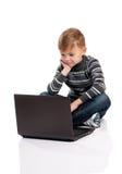 Muchacho que se sienta en piso con el ordenador portátil Imagenes de archivo