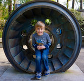 Muchacho que se sienta en rueda hidráulica Fotos de archivo