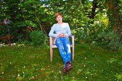 Muchacho que se sienta en su jardín fotografía de archivo