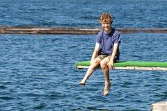 Muchacho que se sienta en tarjeta de salto en el lago Imagen de archivo