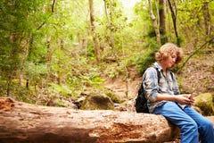 Muchacho que se sienta en un árbol caido en un bosque usando un smartphone Imagenes de archivo
