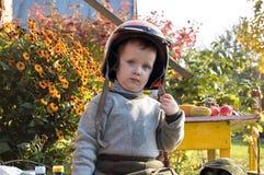 Muchacho que se sienta en un casco de la motocicleta Imágenes de archivo libres de regalías