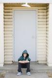 Muchacho que se sienta en un encintado Foto de archivo