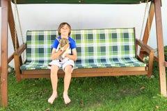 Muchacho que se sienta en un oscilación del jardín con el perro Foto de archivo
