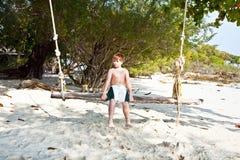 Muchacho que se sienta en un oscilación en la playa Fotos de archivo