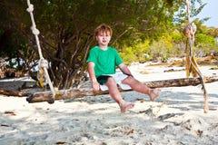 Muchacho que se sienta en un oscilación en la playa Fotografía de archivo libre de regalías