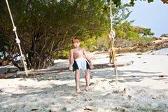 Muchacho que se sienta en un oscilación en la playa Imagen de archivo libre de regalías