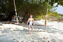 Muchacho que se sienta en un oscilación en la playa Imagenes de archivo