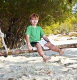 Muchacho que se sienta en un oscilación en una playa tropical Imagen de archivo