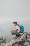 Muchacho que se sienta en un pico de montaña Imagenes de archivo