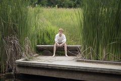 Muchacho que se sienta en un registro cerca de hierba alta en un lago Fotografía de archivo