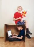 Muchacho que se sienta en una caja de cartón con un ordenador portátil, muchacho que se sienta en la cartulina con un papel color Fotos de archivo