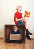 Muchacho que se sienta en una caja de cartón con un ordenador portátil, muchacho que se sienta en la cartulina con un papel color Fotos de archivo libres de regalías