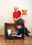 Muchacho que se sienta en una caja de cartón con un ordenador portátil, muchacho que se sienta en la cartulina con un papel color Foto de archivo libre de regalías