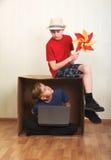 Muchacho que se sienta en una caja de cartón con un ordenador portátil, muchacho que se sienta en la cartulina con un papel color Imagenes de archivo