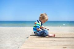 Muchacho que se sienta en una calzada de madera en la playa Imagenes de archivo