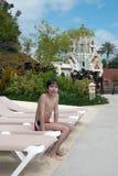 Muchacho que se sienta en una cama de la playa Imágenes de archivo libres de regalías