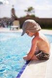 Muchacho que se sienta en una piscina Imágenes de archivo libres de regalías