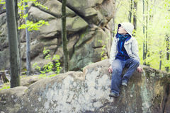 Muchacho que se sienta en una roca Imagen de archivo libre de regalías