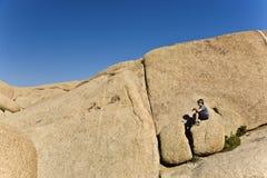 Muchacho que se sienta en una roca en Joshua Tree Nationalpark Fotos de archivo