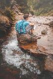 Muchacho que se sienta en una roca en rastro de montaña Imagen de archivo libre de regalías