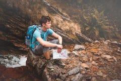 Muchacho que se sienta en una roca en rastro de montaña Foto de archivo