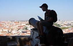Muchacho que se sienta encima de un cañón sobre Lisboa en el sao Jorge de Castelo Imágenes de archivo libres de regalías
