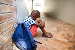 Muchacho que se sienta solamente en el pasillo de la escuela Imagen de archivo libre de regalías