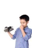 Muchacho que siente infeliz con el calcetín del blanco del mún olor foto de archivo