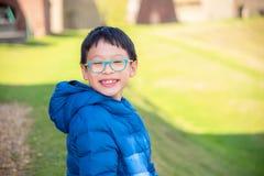 Muchacho que sonríe en el campo de hierba Foto de archivo