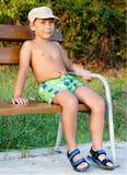 Muchacho que sonríe y que se sienta en banco Fotografía de archivo libre de regalías