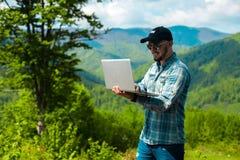 Muchacho que sonríe y que trabaja en el ordenador portátil en las montañas Fotografía de archivo libre de regalías