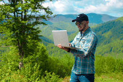 Muchacho que sonríe y que trabaja en el ordenador portátil en las montañas Imagen de archivo libre de regalías