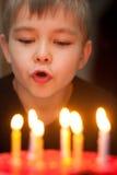 Muchacho que sopla hacia fuera velas en la torta de cumpleaños imagenes de archivo
