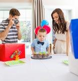 Muchacho que sopla hacia fuera velas en la torta en casa Imagen de archivo