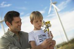 Muchacho que sopla a Toy Windmill With Father Fotos de archivo libres de regalías