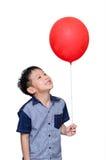 Muchacho que sostiene el globo rojo Imagenes de archivo