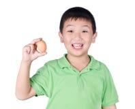 Muchacho que sostiene el huevo de gallina disponible en el fondo blanco aislado Foto de archivo