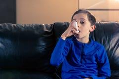 Muchacho que sostiene el inhalador del asma fotos de archivo